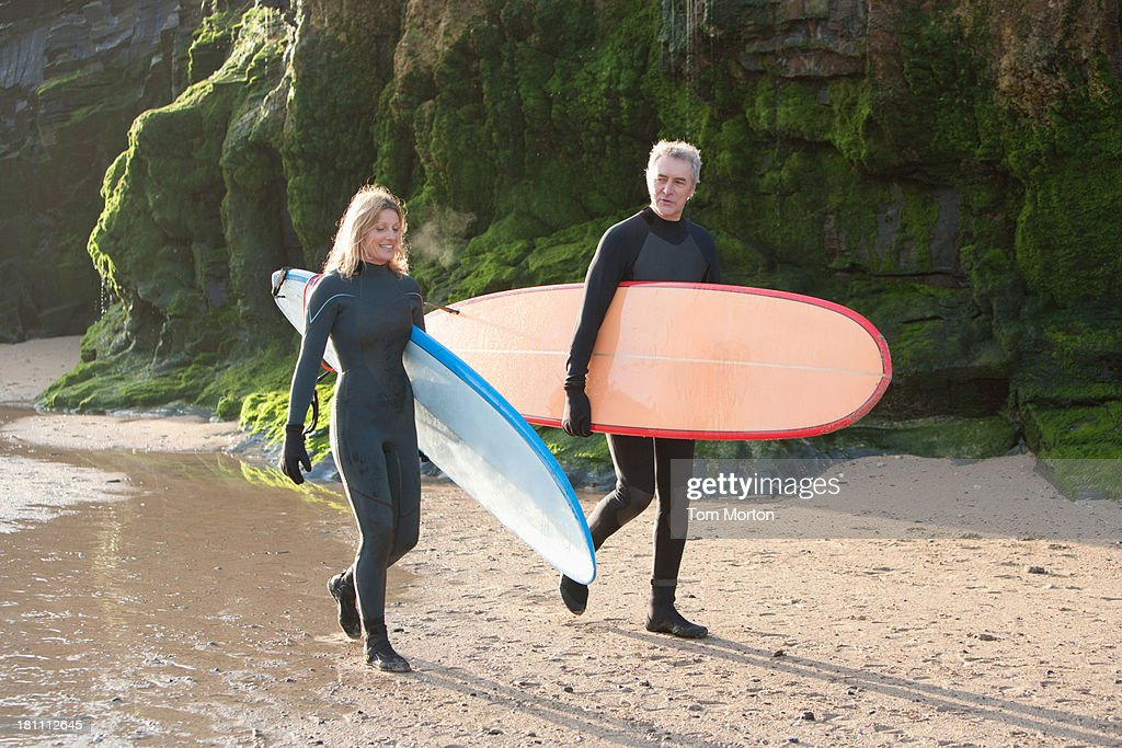 A man and a woman walking down the beach with surfboards : Stock Photo