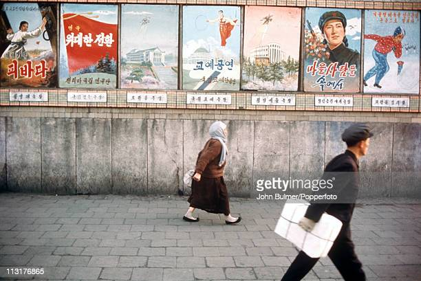 A man and a woman walking past a selection of posters North Korea February 1973