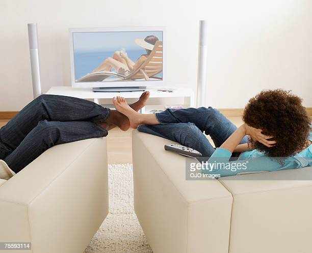 A man and a woman watching television