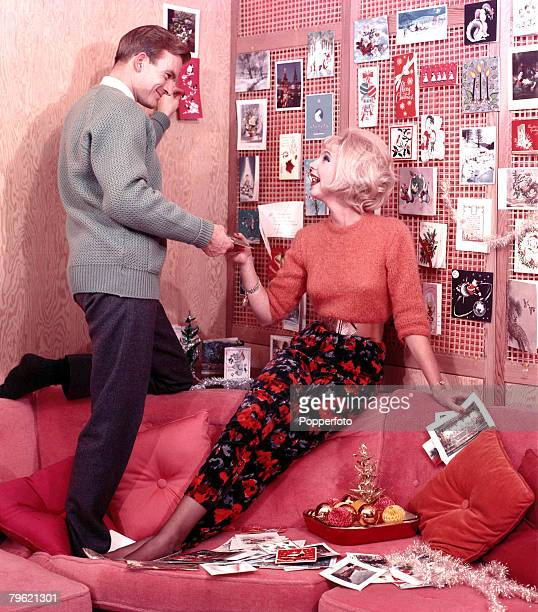 1960 A man and a woman who are on a sofa they are both wearing fashionable clothing whilst pinning up the christmas decorations the woman also has a...