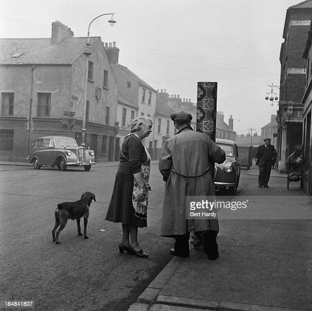 A man and a woman with a roll of lino on a street in Derry Northern Ireland 25th November 1955 Original publication Picture Post 8199 One Man In Five...