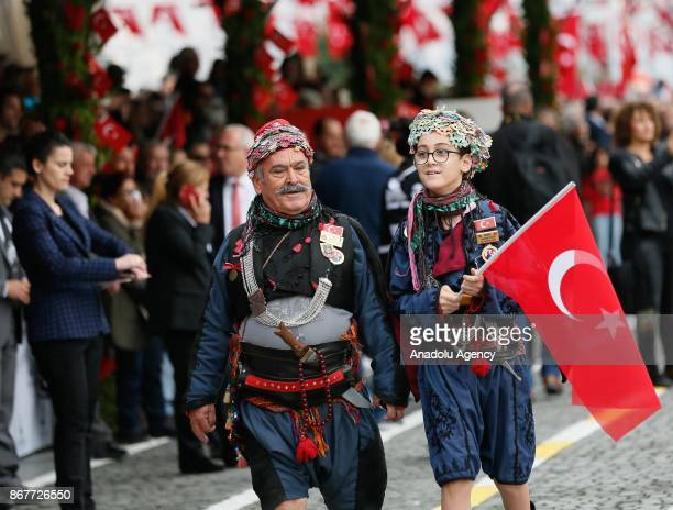 A man and a young girl wearing traditional clothes attend the celebrations for the 94th Anniversary of Republic Day at the Izmir Cumhuriyet Square in...
