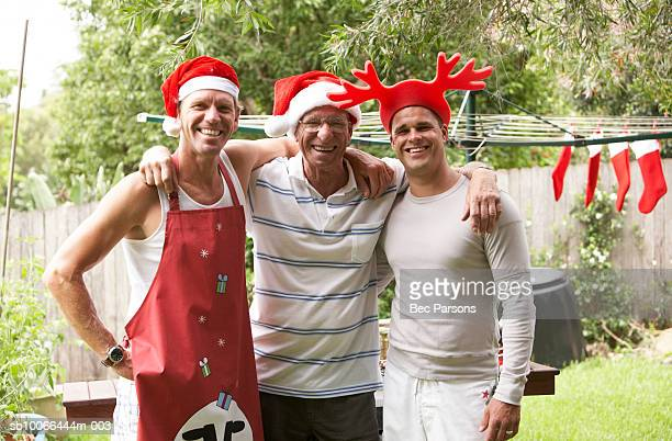 Man and adult sons wearing Christmas hats, embracing in garden