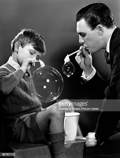 A man and boy blow soap bubbles through clay pipes Images of children are common in the Photographic Advertising archive Photographs of bright...