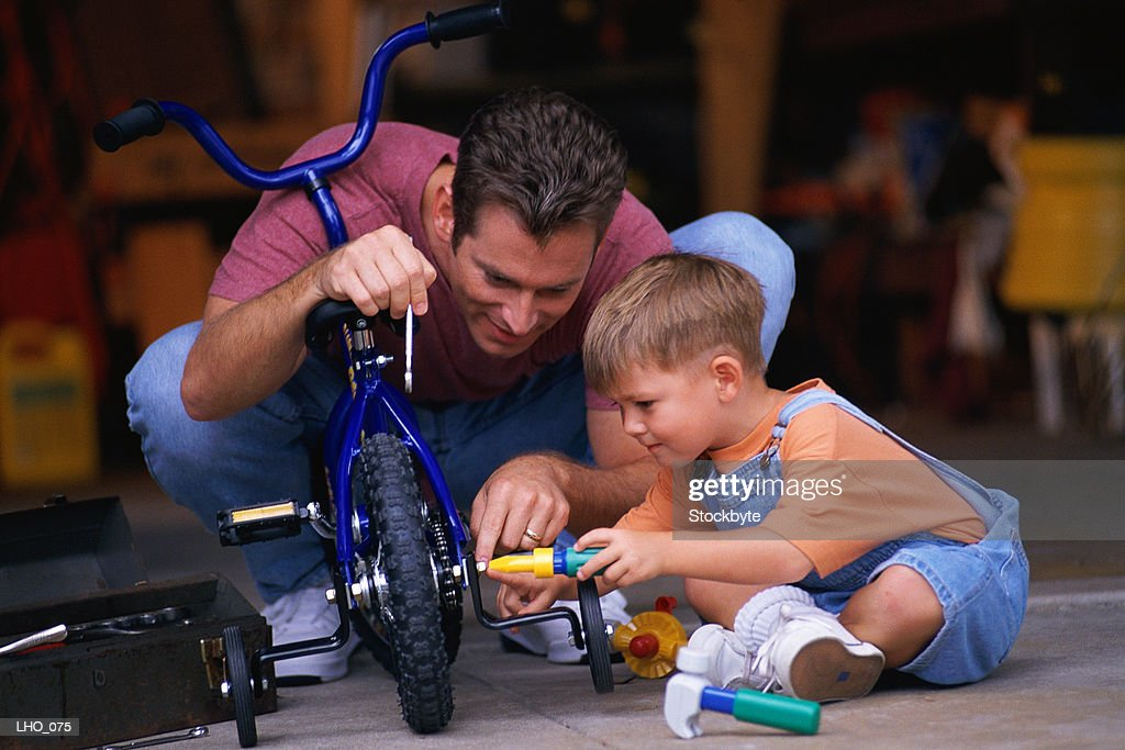 Man and boy fixing tricycle : Stock Photo