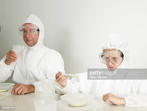Man and boy in protective suits dining