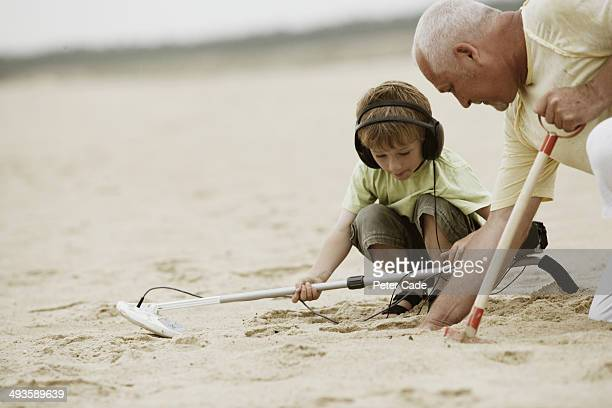 Man and boy on beach with metal detector and spade