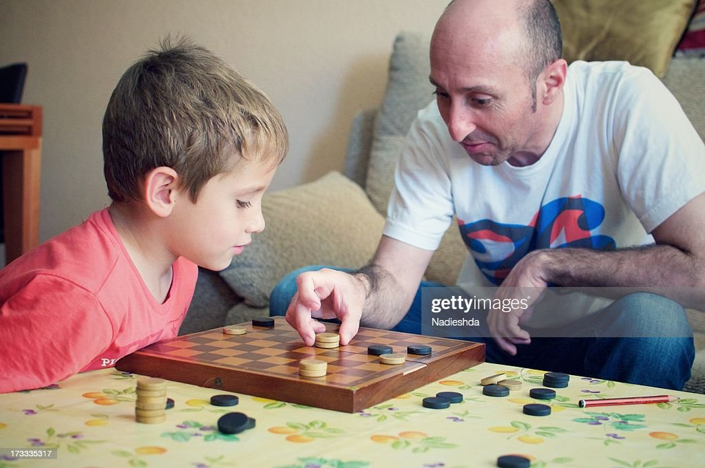 Man and boy playing checkers