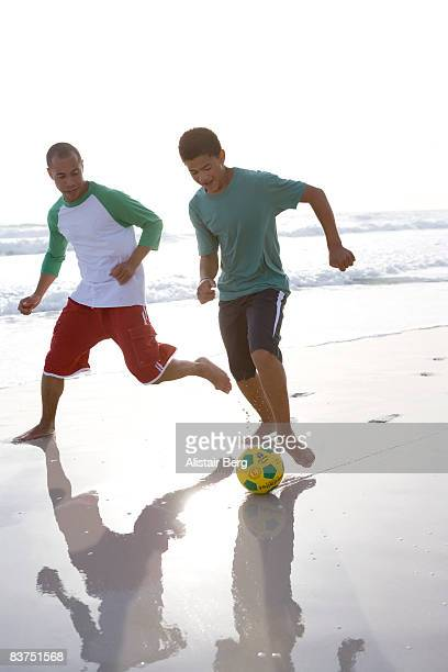 Man and boy playing football on beach