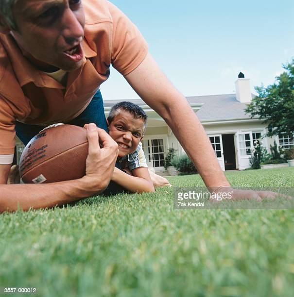 Man and Boy Playing Football