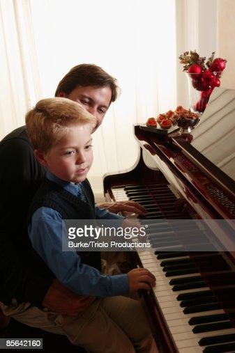 Man and boy playing piano