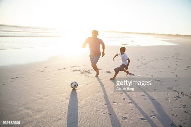 Man and boy playing soccer on a beach