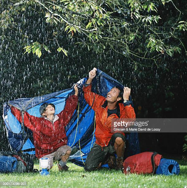 Man and boy (8-10) sheltering under tarpaulin from rain