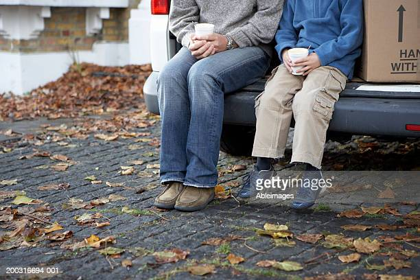 Man and boy sitting in back of van holding cups, low section