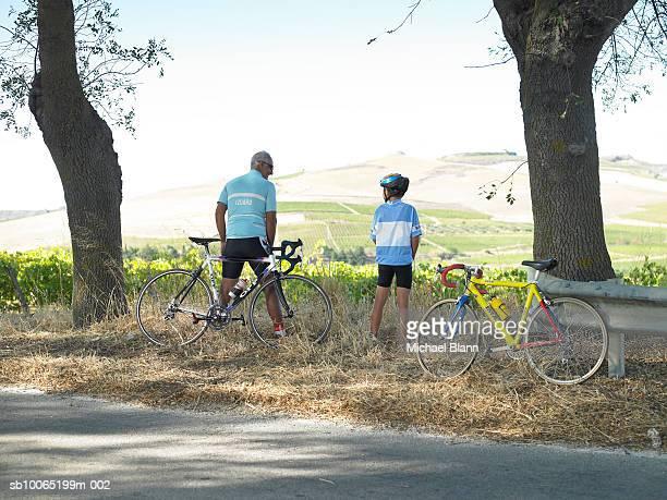 Man and boy (10-11) urinating at roadside, rear view