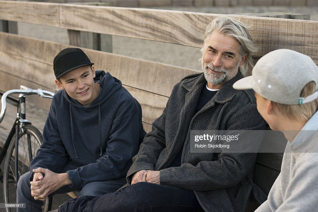 Man and boys sitting talking on bench : Stock Photo