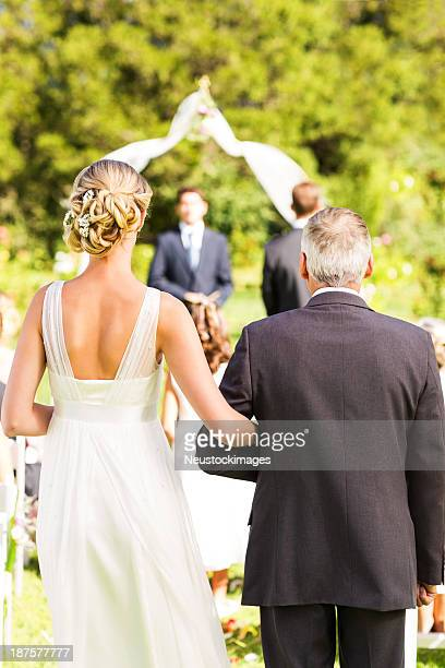 Man And Bride Walking Down The Aisle During Wedding Ceremony