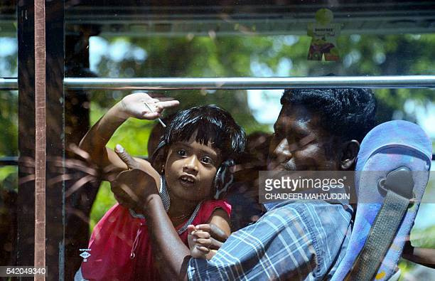 A man and child from Sri Lanka who were stranded on a boat on the west coast of Sumatra island for over a week sit on a bus in Lhoknga in Aceh...