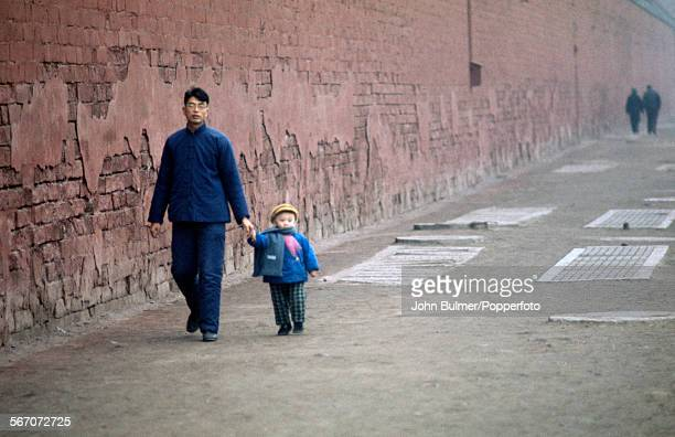 A man and child outside the Forbidden City in Beijing China during the Cultural Revolution 1973