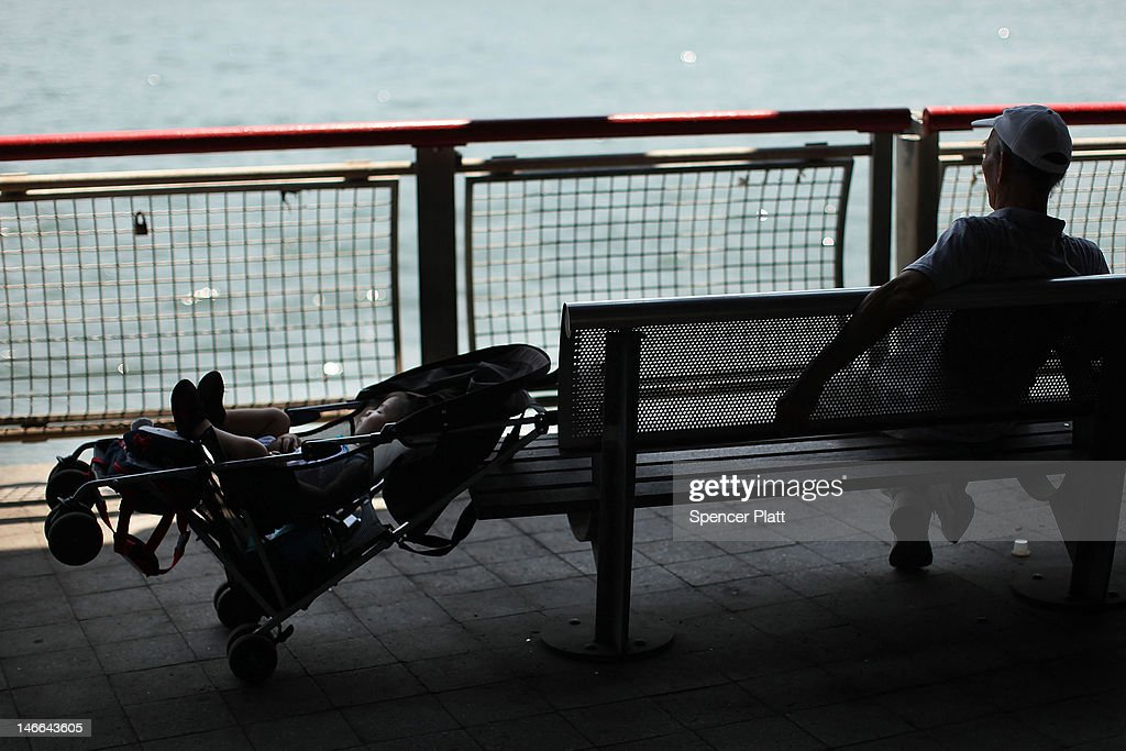 A man and child rest in the shade by the East River during record breaking heat on June 21, 2012 in New York City. New York City and much of the East Coast have been experiencing a second day of hot weather with temperatures of 98 degrees Fahrenheit (37 Celsius) being predicted in Central Park. High heat warnings and air quality alerts have been issued from Quebec to Virginia. Temperatures are not expected to cool down until the start of next week.