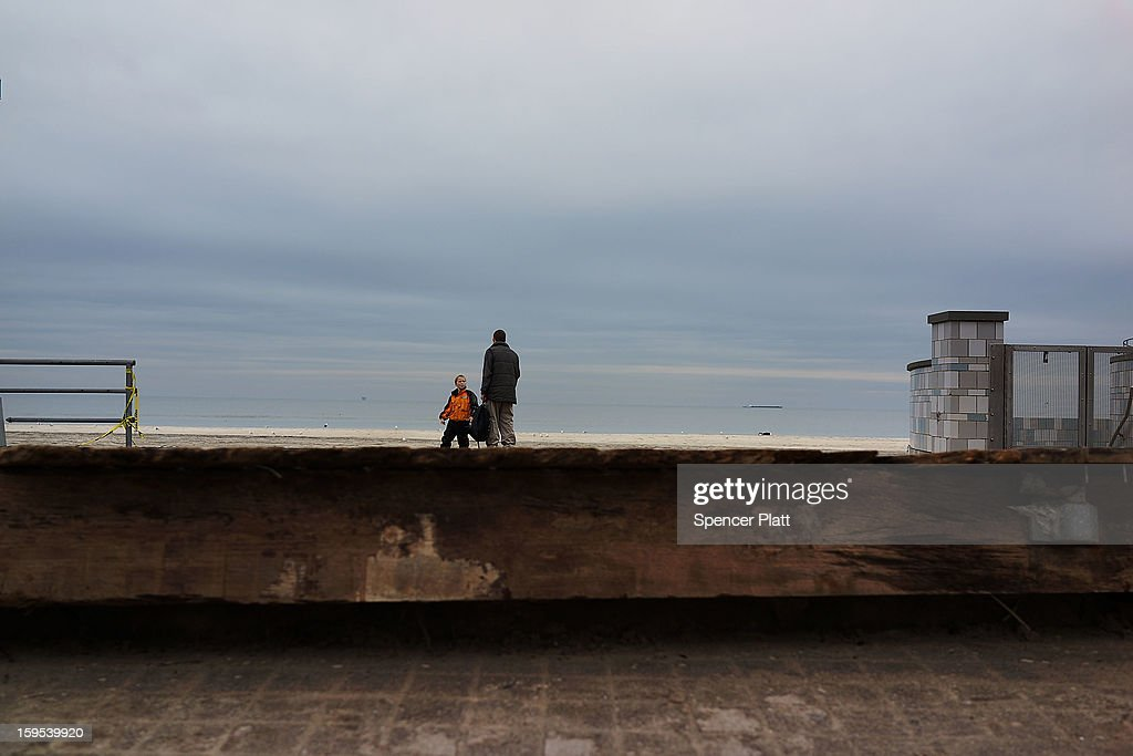 A man and child stand near a boardwalk damged during Hurricane Sandy in the Rockaways on January 15, 2013 in the Queens borough of New York City. A $50.7 billion Superstorm Sandy aid package is expected to be voted on today in the House. The package, which has come under criticism by some fiscal conservatives, is being heavily pushed by Northeastern lawmakers. The money would be spent on immediate needs to the region including $5.4 billion for New York and New Jersey transit systems and $5.4 billion for the Federal Emergency Management Agency's disaster relief aid fund.