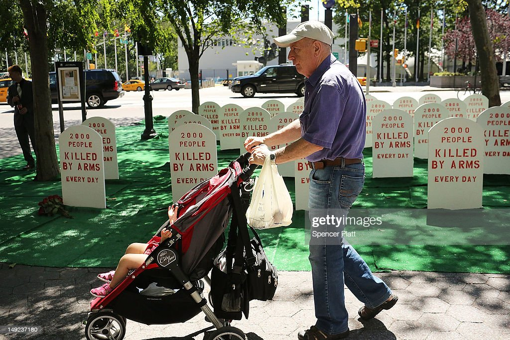 A man and child walk by a mock graveyard across from the United Nations (UN) which represents those killed by arms everyday around the world on July 25, 2012 in New York City. The group Control Arms set up the campaign to help draw attention to the issues of deaths by guns and other armaments while negotiations continue at the UN for a new Arms Trade Treaty.