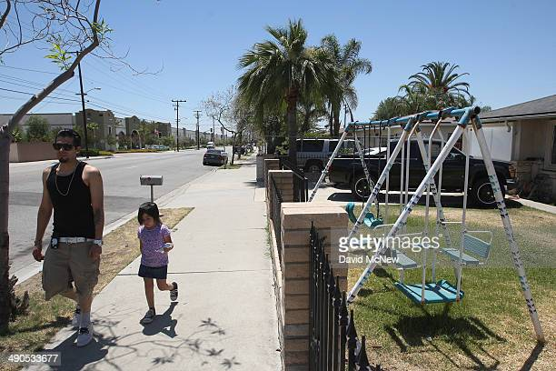 A man and child walk near houses across the street from the Huy Fong Foods Sriracha Hot Chili Sauce factory on May 14 2014 in Irwindale California...