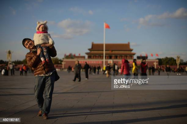 A man and child walk on Tiananmen Square in Beijing on November 17 2013 On November 15 China's Communist rulers announced an easing of the country's...