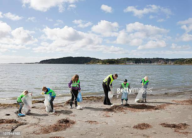 Man and children cleaning beach