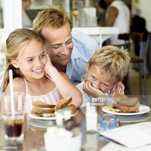 man and children in a cafe (6-10)
