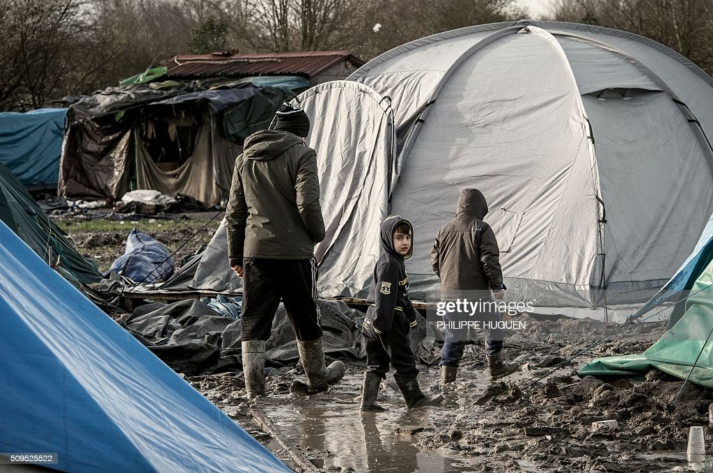 A man and children walk in the so-called 'Jungle' migrant camp in Gande-Synthe where 2,500 refugees from Kurdistan, Iraq and Syria live on February 11, 2016 in Grande-Synthe near the city of Dunkirk, northern France. / AFP / PHILIPPE HUGUEN