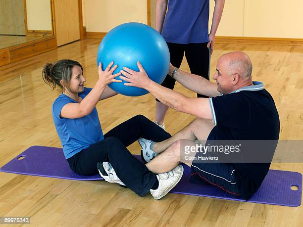 man and daughter exercise at gym