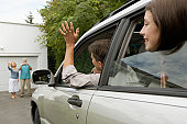 Man and daughter (13-15 years) in car waving to senior couple on drive