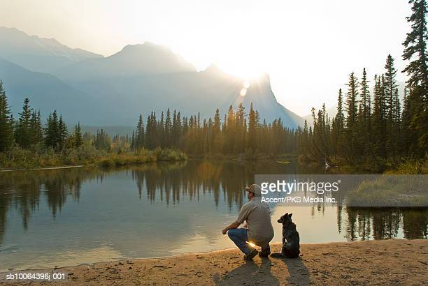 Man and dog beside lake in mountains, rear view