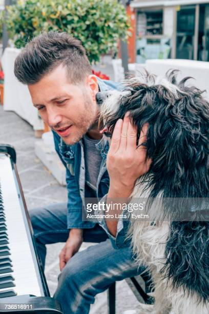 Man And Dog By Piano Outdoors