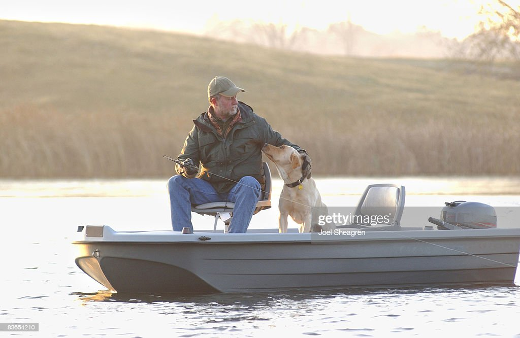Man and dog fishing from small boat.