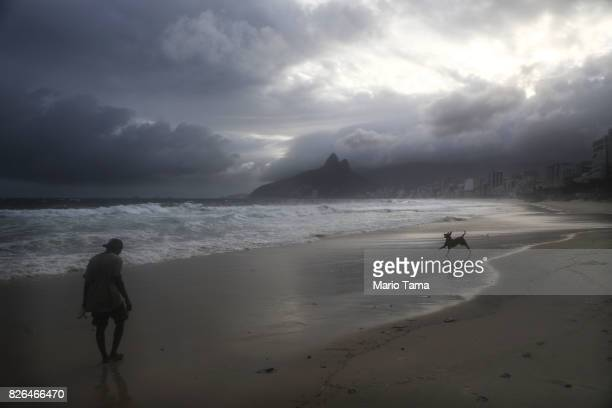 A man and dog have Ipanema beach to themselves in the midst of a winter cold front on August 4 2017 in Rio de Janeiro Brazil Temperatures were...