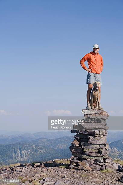 Man and dog on top of mountain cairn.