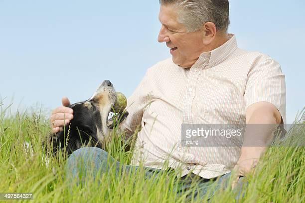 Homme et chien assis dans l'herbe