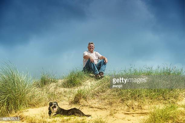 Man and dog, sitting/lying in sand dunes