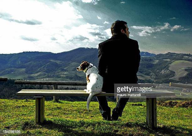 Man and dog sittting on bench