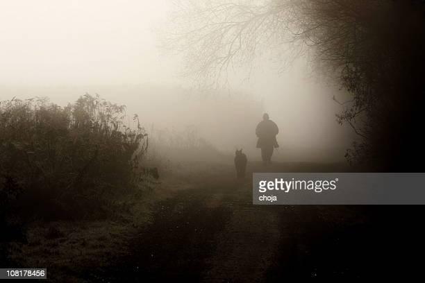 Homme et chien marchant le long chemin de terre dans le brouillard