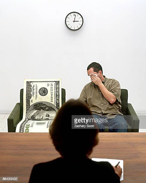 Man and Giant 100 dollar bill see therapist