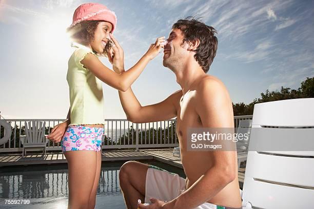 Mann und Mädchen Anwendung Sonnencreme auf Nase