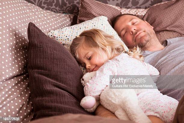 Man and girl asleep in bed