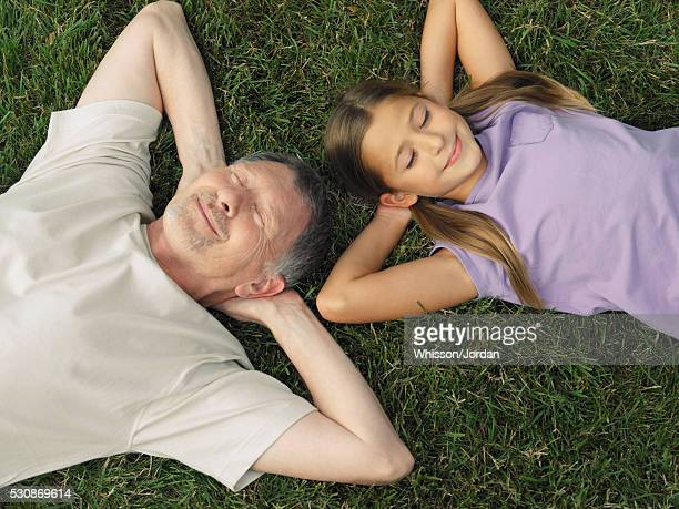 Man and girl lying down on lawn