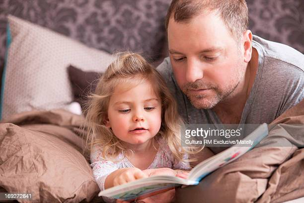 Man and girl lying in bed reading book