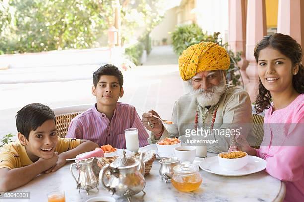 Man and grandchildren eating breakfast together