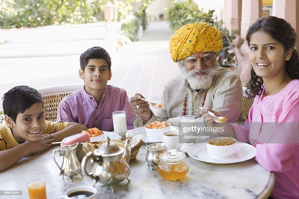 Man and grandchildren eating breakfast together : Stock Photo