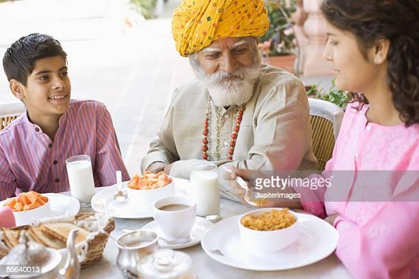 Man and grandchildren eating together